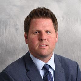 headshot of Kevin Sullivan on a gray background